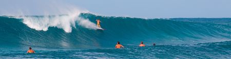 Surfers surf some large waves on the north shore of Oahu Hawaii. Imagens