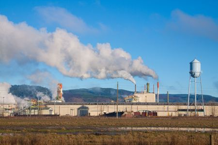 A paper mill in Oregon emits smoke and pollution into the clean air and blue sky overhead. photo