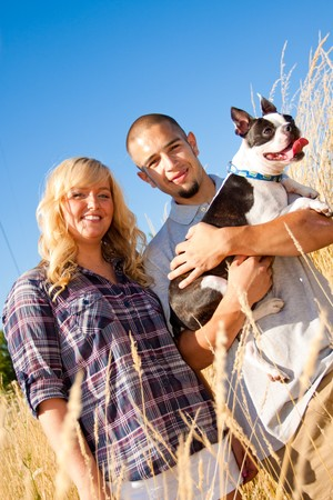 A young engaged couple and their boston terrier dog. photo