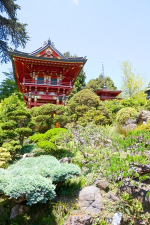 A bright red Japanese pagoda building in a tea garden sits peacefully.