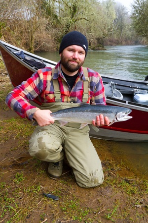 A steelhead fisherman holds his trophy fish by his boat and the river in Oregon. photo