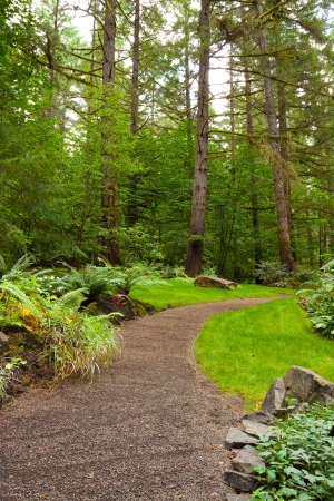 A beautiful path leads into a perfectly manicured garden at an Oregon wedding venue location  There is green, trees, plants, and stone in this vertical image  photo