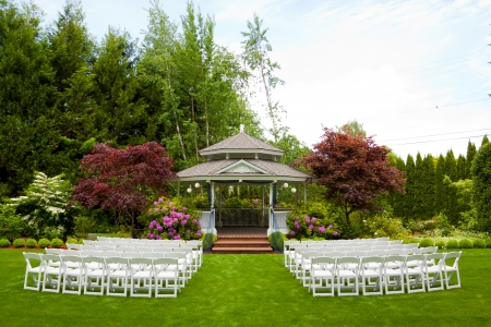 A gazebo and white chairs at a wedding venue for the ceremony and reception  Фото со стока