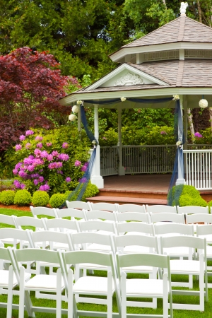 A gazebo and white chairs at a wedding venue for the ceremony and reception  Stockfoto