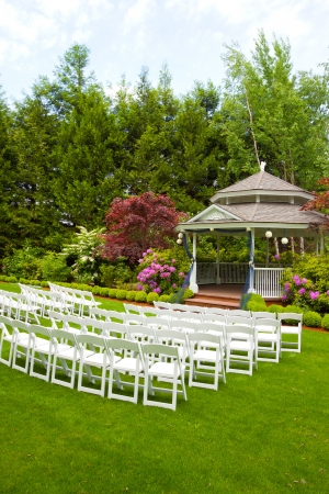 A gazebo and white chairs at a wedding venue for the ceremony and reception  photo