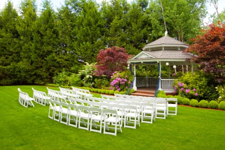 A gazebo and white chairs at a wedding venue for the ceremony and reception  版權商用圖片