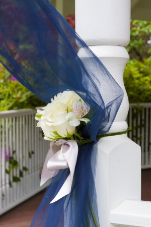 Wedding decor ribbon in blue on the post of a gazebo at an outdoor venue