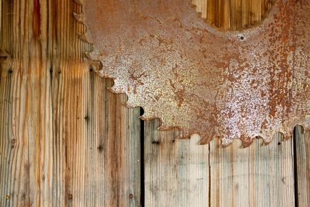 Een roestige zaagblad is opgehangen aan een houten muur om een interessante en unieke abstracte achtergrond afbeelding te creëren met veel kopie ruimte voor design