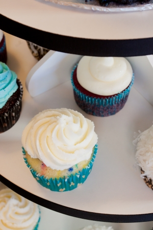 Several cupcakes on a serving table at a wedding ceremony and reception  The colors here are black, blue, and white  photo