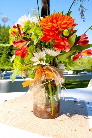 Wit, oranje en groen bruiloft bloemstukken met jute als de centerpieces voor tafelaankleding in een openlucht receptie. Stockfoto