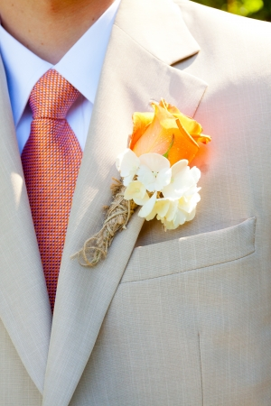 A groom in a light-colored suit is ready for his wedding day in formal attire with a boutineer on his jacket lapel. photo