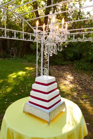 A white and red square wedding cake with multiple tiers and the letter R on top sits outside on a yellow table for a wedding reception  photo