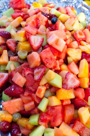 fruit platter: A healthy platter of fruit at a wedding buffet  This image is in color and a vertical composition  It includes strawberries, watermelon, pineapple, honeydew, melon, grapes, blueberries, and more  Stock Photo