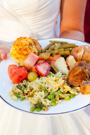 The meal of a bride on her wedding day looks healthy and cooked well with potatoes, fruit, pasta salad, green beans, chicken and more  photo