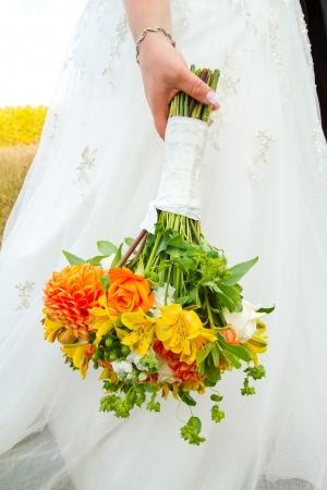A bride in her white wedding dress holds her bouquet of orange, green, and yellow flowers on her wedding day  Reklamní fotografie