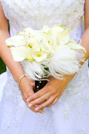 A beautiful bride in her white wedding dress holds her bouquet of flowers on her wedding day.