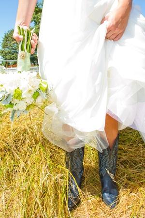 Een bruid draagt haar bont en blauw cowboy (of cowgirl) laarzen op haar trouwdag. Stockfoto