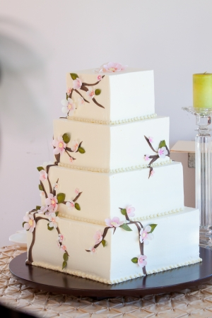A very traditional white wedding cake at the reception for a bride and groom on their wedding day. Stock Photo