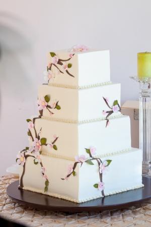 pastel boda: Un pastel blanco boda muy tradicional en la recepción para una novia y el novio en su día de boda.