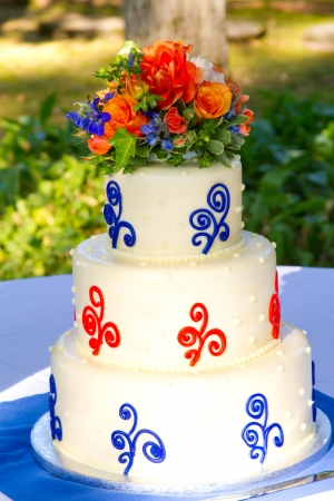 topper: A very traditional white wedding cake at the reception for a bride and groom on their wedding day. Stock Photo