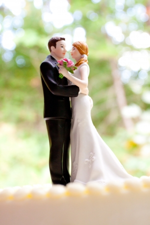topper: A bride and groom cake toppers stands atop this traditional white wedding cake at a reception in the woods or forest.