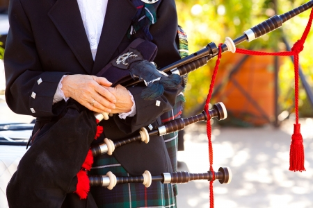 A woman holds her bagpipes at a traditional Scottish wedding.