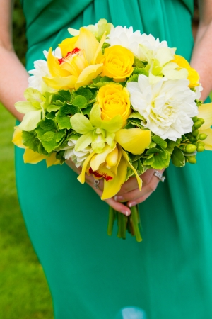 A bridesmaid in a teal green dress holds a bouquet of flowers during a wedding.