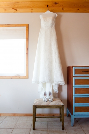 suite: A wedding dress hangs in the bridal suite with wedding shoes before the bride gets ready.