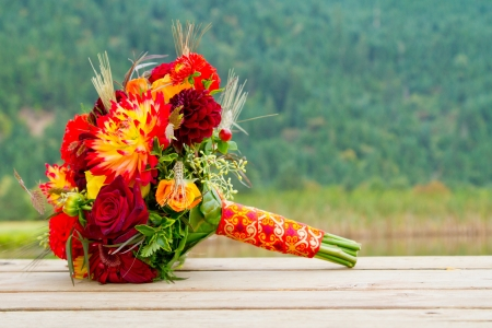 A brides wedding bouquet sits on a wooden dock with a scenic backdrop of mountains and trees. Stock Photo
