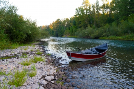 A red drift boat is anchored along the river bank during a day of floating and fishing  Imagens
