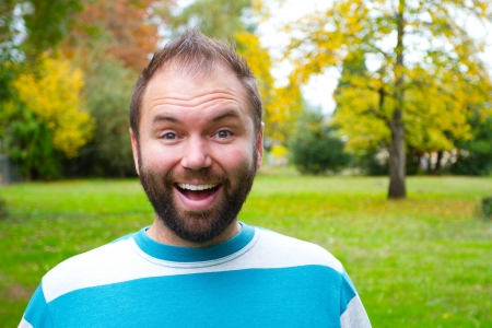 A portrait of a smiling man with a full beard outdoors in a park setting. Stock Photo - 17078204