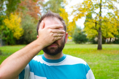 A man with a full beard covers his eyes and face while outdoors in a park setting.