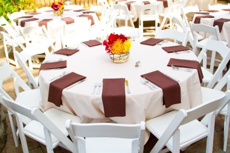 Place settings, tables, and chairs are empty before the guests arrive at a wedding reception. Imagens