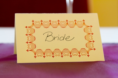 nametag: This name tag says bride to reserve her spot at a wedding dinner table.