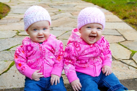 beanies: Two twin baby girls sit on a stone walkway wearing pink sweatshirts and beanies.