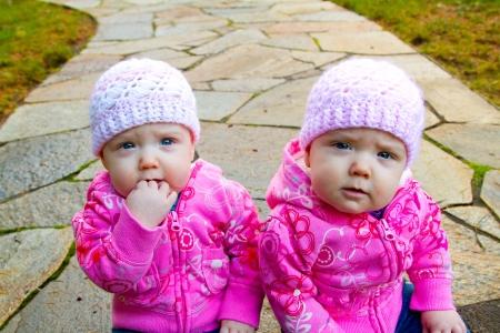 beanies: Dos ni�as gemelas sentarse en una calzada de piedra que llevaba camisetas de color rosa y gorros. Foto de archivo