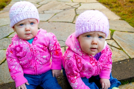 Two twin baby girls sit on a stone walkway wearing pink sweatshirts and beanies.