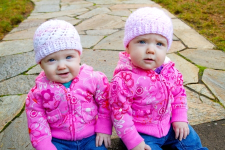 sweatshirts: Two twin baby girls sit on a stone walkway wearing pink sweatshirts and beanies.
