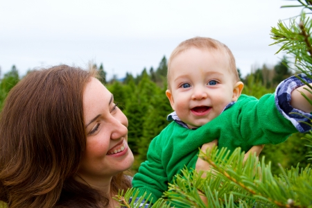 A cute young boy in a green shirt is having fun at a Christmas tree farm in Oregon. photo