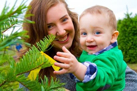 Een leuke jonge jongen in een groen shirt wordt met plezier op een kerstboom boerderij in Oregon.