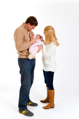 newborn baby girl: A family portrait of three people in the studio including mother father and newborn baby girl. Stock Photo