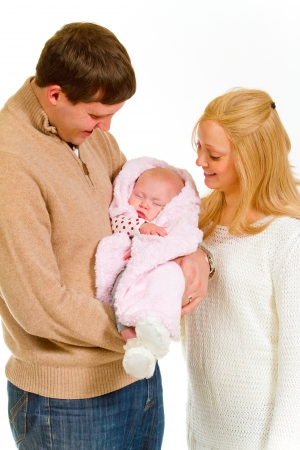A family portrait of three people in the studio including mother father and newborn baby girl. photo