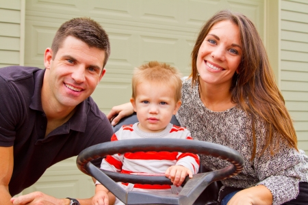 A husband and wife have their first child and pose for a portrait with the boy.