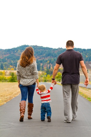 A family walks away on a path while holding hands with the child in the middle. photo