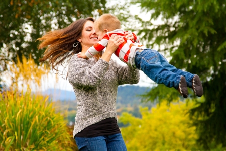 happy moment: A woman spins her child around while holding him in the air in this joyous happy moment.