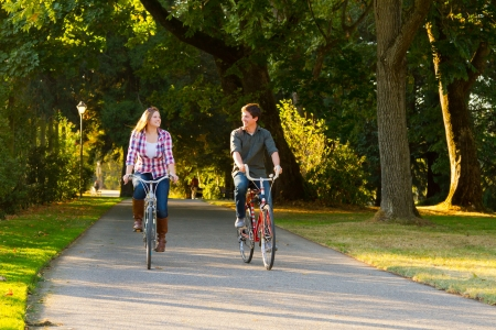A man and a woman with their bicycles on a bike path in an outdoor park setting.