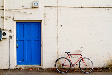 industrial park: A bright blue door contrasts with this bike leaned up against the white wall.