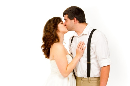 An attractive woman and her handsome husband wear their wedding attire in the studio agains an isolated white background.