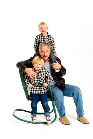 A grandfather with two boys in the studio on an isolated white background with a green rocking chair. Stock Photo - 17514913