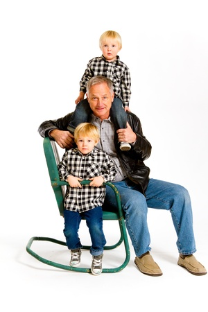 A grandfather with two boys in the studio on an isolated white background with a green rocking chair. Stock Photo - 17514969
